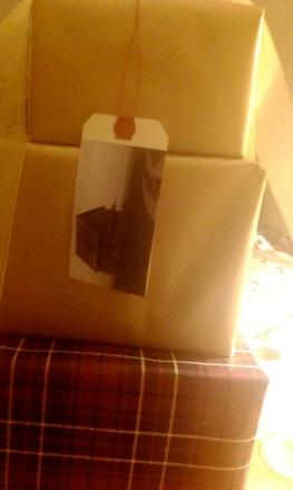 Stack of presents wrapped in plain brown kraft paper and tartan, with DIY photograph luggage tag